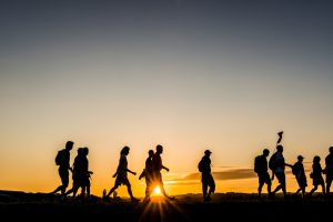 The Netherlands - Participants in a walking event walk in the first sunlight on a dike in the Netherlands.